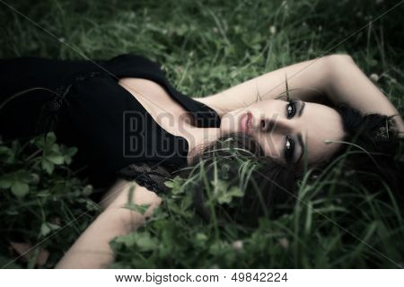 beautiful elegant mature woman lie in grass