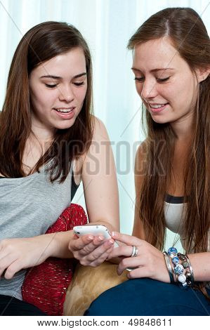 Two Girls Looking At A Phone.