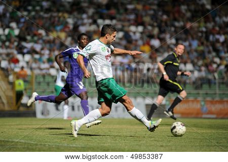 KAPOSVAR, HUNGARY - AUGUST 16: Okuka Drazen (in white) in action at a Hungarian National Championship soccer game - Kaposvar (white) vs Ujpesti TE (purple) on August 16, 2013 in Kaposvar, Hungary.