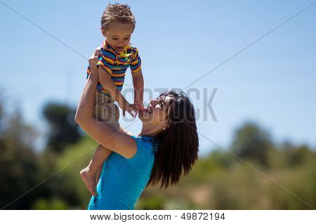 Beautiful mother holding her son in the air