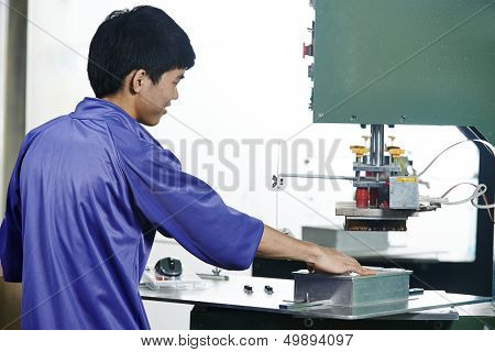 chinese worker operating press in china production factory manufacturing