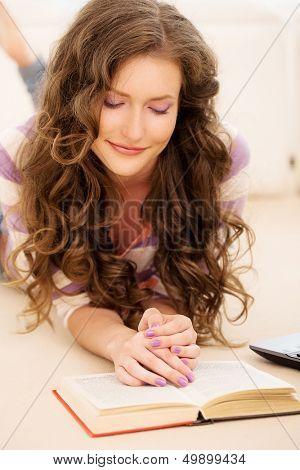 Porträt eines beautful Mädchens, ein Buch, beim liegen auf dem Boden lesen ist