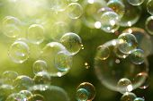 Soap bubbles floating in the air as the Summer sun sets poster