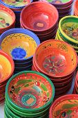pottery in traditional provencal colors and patterns at a market in the provence poster