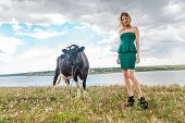 Young woman and a cow in the countryside poster