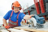 Male builder working with power tool circular saw machine cutting plastic parts at construction site poster