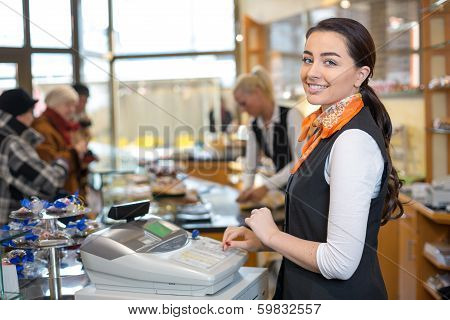 Shopkeeper And Saleswoman At Cash Register Or Cash Desk
