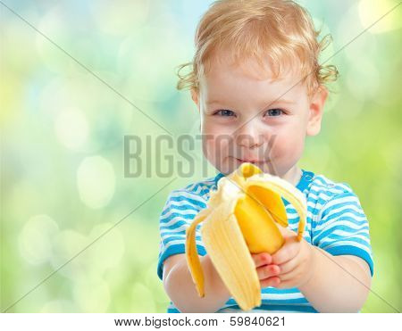 happy kid eating banana fruit. healthy food eating concept.