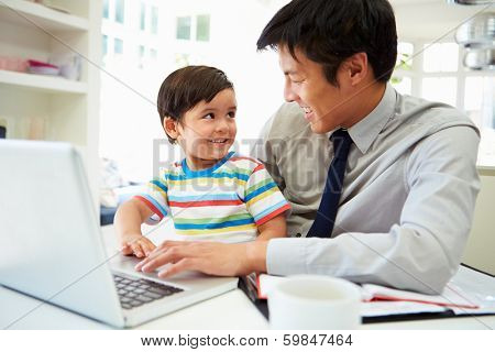 Busy Father Working From Home With Son