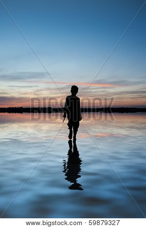 Concept Image Of Young Boy Walking On Water In Sunset Landscape