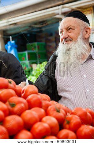 Jerusalem, Israel - November 15, 2012: Elderly Jewish man is shopping for produce at Mahane Yehuda - famous market in Jerusalem