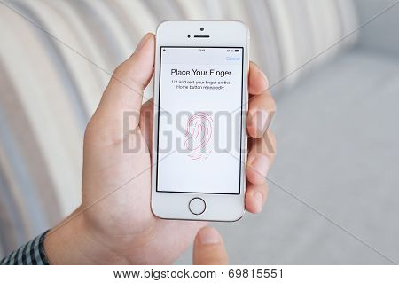 Man Holding A White Iphone 5S With Touch Id On The Screen