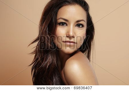 Latin Woman With Ideal Skin On A Beige Background