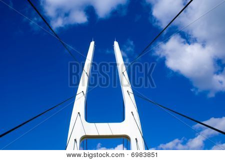 A White Suspension Bridge Against A Blue Sky With Clouds