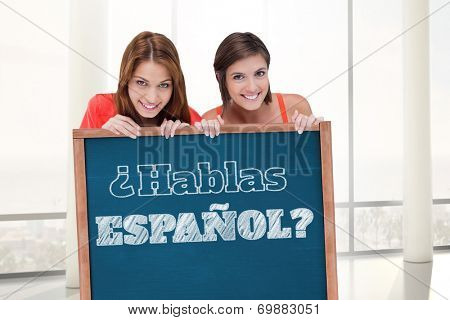 Teenage girls smiling while holding a blank poster and hiding behind it against blackboard with copy space on wooden board, Do you speak Spanish?