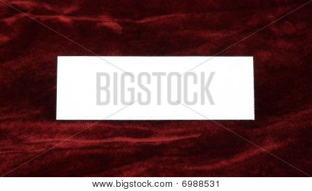 A white invitation card on a crushed velvet background