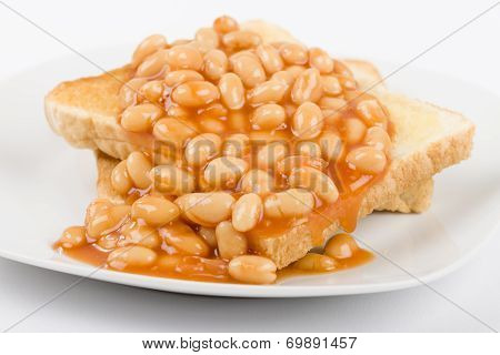 Beans on Toast - Slices of toasted white bread, buttered and topped with baked beans. Simple British breakfast meal. poster