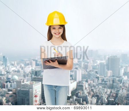childhood, construction, architecture, building and people concept - smiling little girl in protective helmet with clipboard making notes