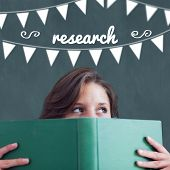 The word research and bunting against student holding book poster