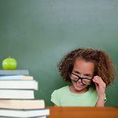 Cute pupil tilting glasses against green apple on pile of books poster