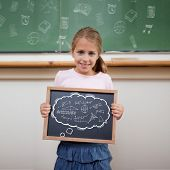 Math in thought bubble against cute pupil showing chalkboard poster