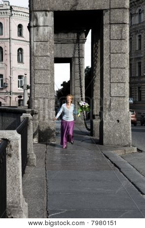 woman runs with Bouquet through bridge over the river
