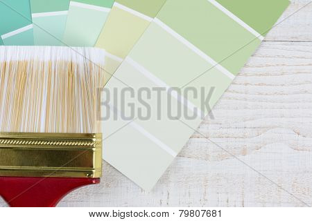 Overhead shot of  a paint brush and shades of green color samples on a rustic white wooden surface. Horizontal format with copy space.