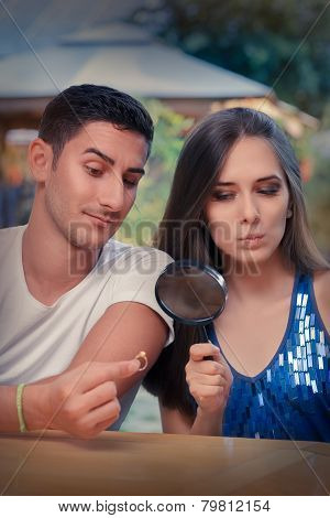 Curious Girl Testing Engagement Ring from Boyfriend with Magnifier