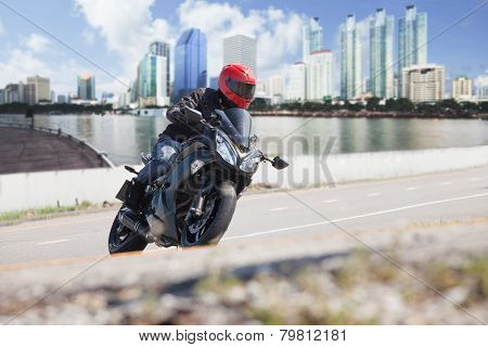 Young Man Riding Big Bike Motorcycle On City Road Against Urban And Town Building Scene Background U