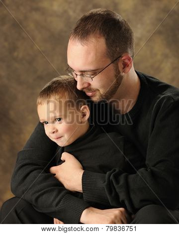 A happy preschool boy with his dad's arms wrapped snugly around him.