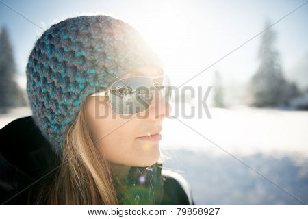 cool girl with cap looking to winter landscape through sunglasses