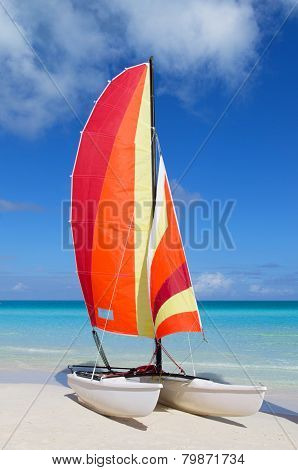 Catamaran With Its Colorful Sails Wide Open On Cuban White Sandy Beach