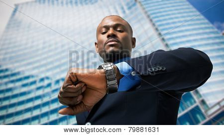 Handsome businessman looking at his watch