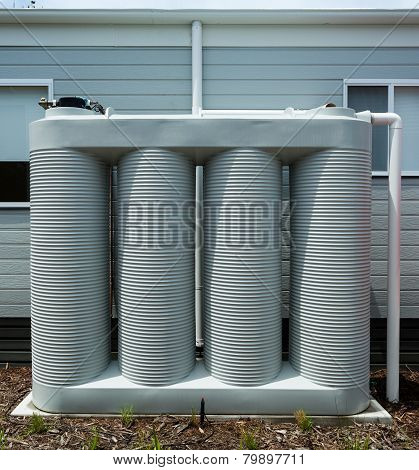 Rainwater collection tank besides a modern house poster