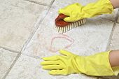 hands in rubber gloves scrubbing the tiles poster