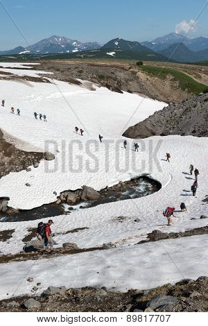 Group Of Tourists Traverse Mountain River On Snowfield. Kamchatka, Far East, Russia