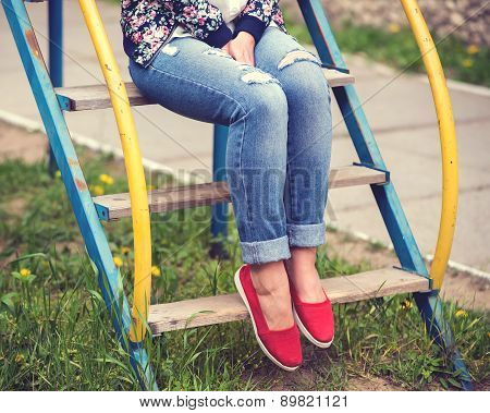 Girl sits on playground chute