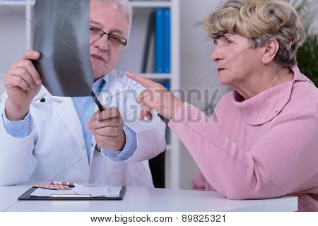 Elder practitioner analyzing with patient chest x-ray poster