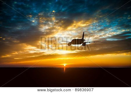 Airplane in the sky at sunset clouds