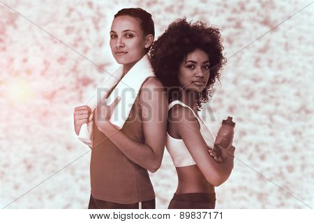 Fit women standing with waterbottle and towel against dark grey texture