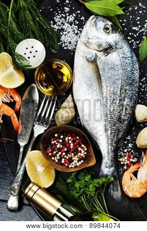 Delicious fresh fish and seafood on dark vintage background. Fish, cockles and  shrimps with aromatic herbs, spices and vegetables - healthy food, diet or cooking concept