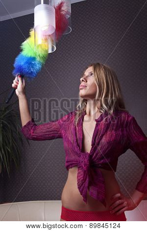young beautiful woman maid dusting on pendant luminaire