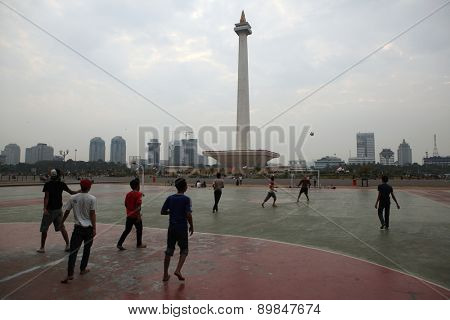 JAKARTA, INDONESIA - AUGUST 17, 2011: Children play football at the foot of the National Monument or the Monas in Jakarta, Central Java, Indonesia.