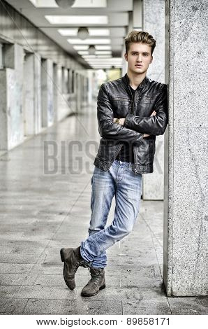 Young man with leather jacket standing outside against pillar