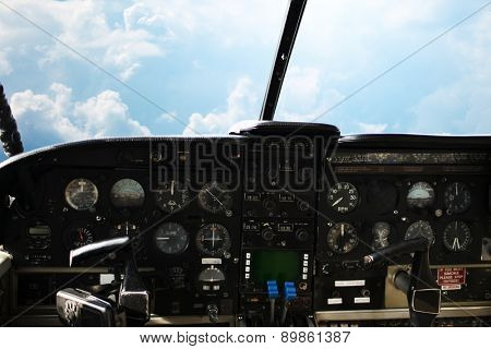 air transport, travel, technology and aviation concept - dashboard in airplane cockpit and view of cloudy sky behind windshield
