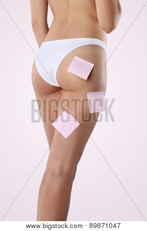 Bum and legs of slim woman over pink background with post it