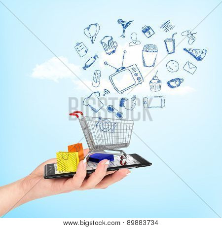 Online Shop Concept. Female Hand Holding A Phone On Which Stands Empty Shopping Cart With Falling Dr
