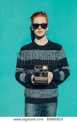 Young redhead man in a sweater and jeans and sunglasses standing next to turquoise wall and taking p