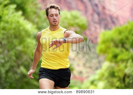 Runner looking at heart rate monitor smartwatch while running. Man jogging outside looking at his sports smart watch during workout training for marathon run. Fit male fitness model in his 20s.