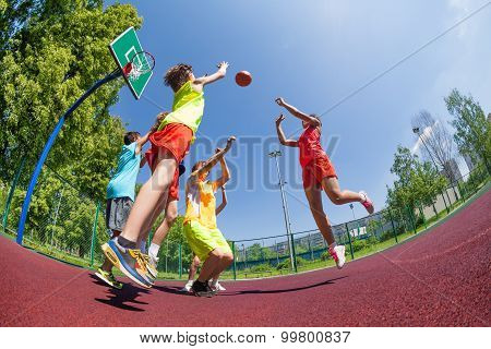 Fisheye view of teenagers playing basketball game